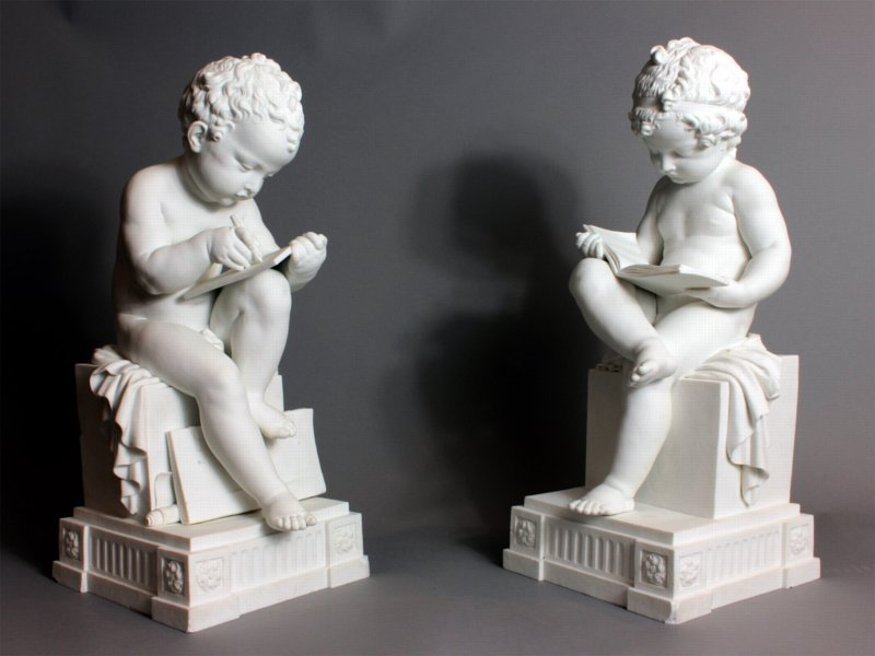 Dihl and Guérard biscuit figures depicting a boy reading and a girl writing.